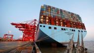 Ein riesiges Containerschiff der Linie Maersk liegt in Schanghai vor Anker.