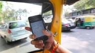 Die Entwicklung von Volkswirtschaften profitiert von der Globalisierung, glaubt die BIZ. Unser Bild zeigt einen indischen Rikschafahrer, der eine Smartphone-App nutzt.