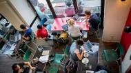 Gäste arbeiten in Berlin-Mitte im Cafe St. Oberholz an ihren Laptops im Internet.