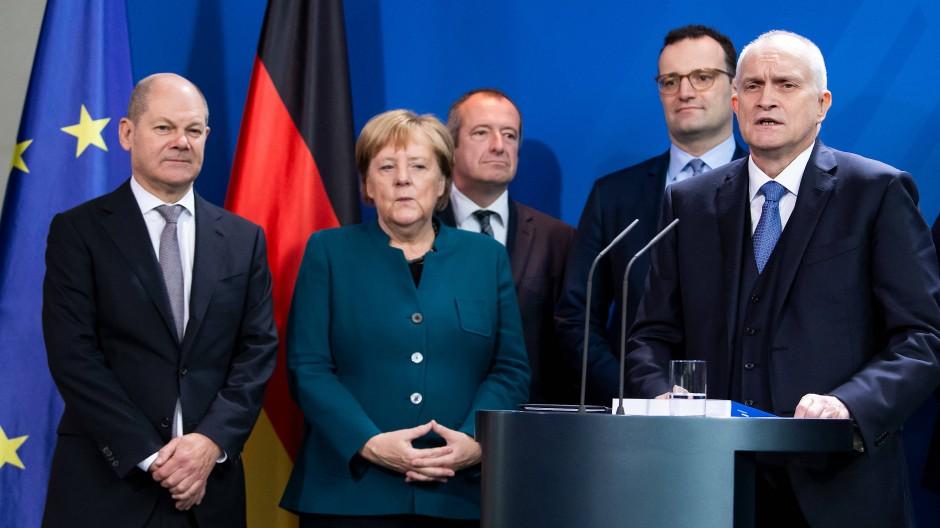 Puh, Glück gehabt? Kanzlerin Merkel und Mitglieder ihrer Regierung bei der Übergabe des Gutachtens. Am Mikrofon Christoph Schmidt, Vorsitzender des Sachverständigenrates.
