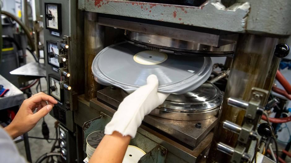 Eine Schallplatte wird aus der Presse genommen.