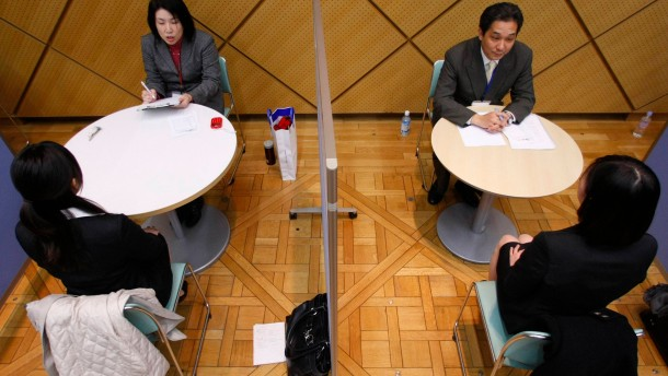 Women in suits take part in a workshop to practise job interview skills in Tokyo