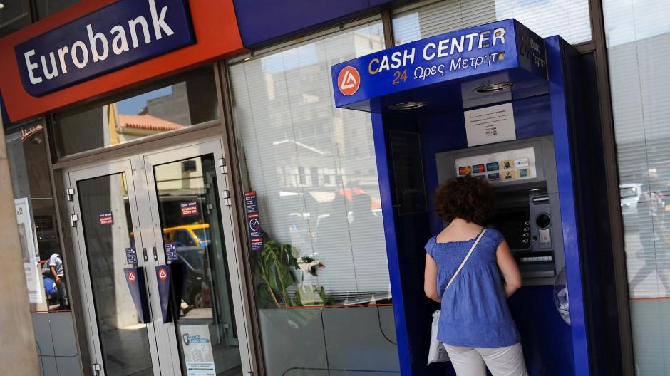 Eine Frau steht an einem Athener Geldautomaten der vom Kursrutsch betroffenen Eurobank.