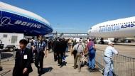 Besucher der Luftfahrtmesse im französischen Le Bourget gehen zwischen einer Boeing 777 (links) und einem Airbus A340 hindurch.