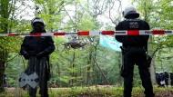 Polizisten in Schutzausrüstung stehen an einer Absperrung im Hambacher Forst.