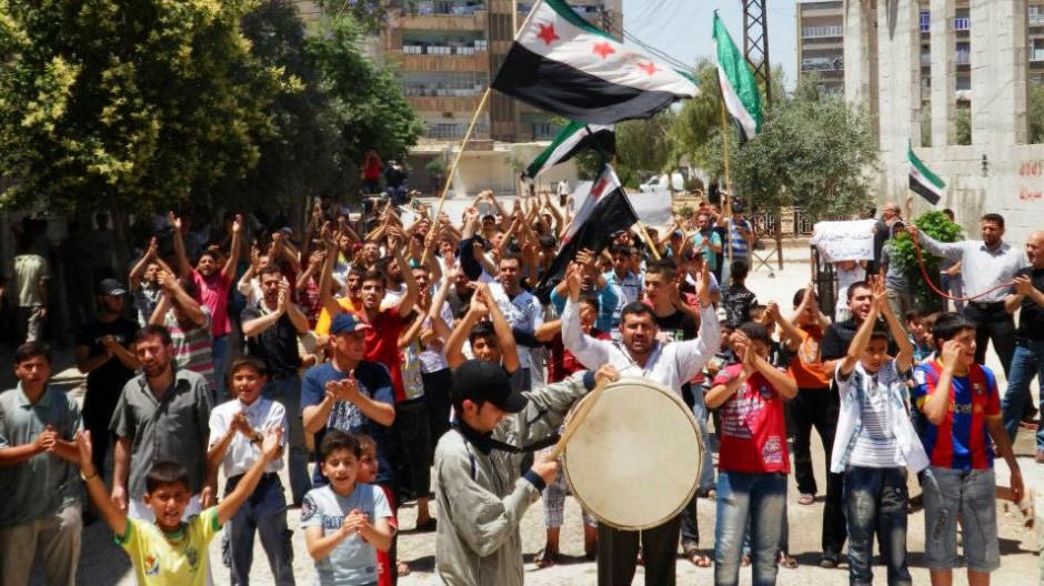 In der Provinz Hama protestieren Teilnehmer einer Beerdigung gegen das Regime des syrischen Präsidenten al Assad.