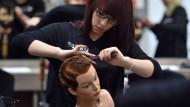 Geübt wird zunächst an einem Puppenkopf: Friseurlehrling verdienen wenig