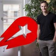 Niklas Oestberg, CEO von Delivery Hero, neben seinem Firmenlogo im Hauptsitz des Unternehmens an der Oranienburger Straße in Berlin-Mitte.