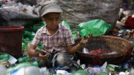 Ein elfjähriger Junge in Bangladesch sortiert Plastikflaschen in einer Recylingfabrik. Das Sortieren von Plastik ist ein wachsendes Geschäft.