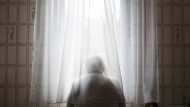 Draußen ist es schöner: Eine Rentnerin schaut aus dem Fenster.