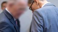 Ein ehemaliger Manager des Panzerbauers Krauss-Maffei Wegmann, Olaf E. (l), unterhält sich im Landgericht in München mit seinem Rechtsanwalt Rainer Spatscheck.