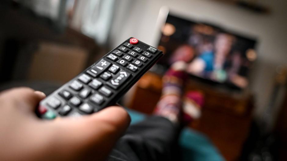 in junger Mann sitzt mit einer Fernbedienung vor dem Fernseher.