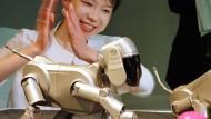 """Am 11. Mai 1999 freut sich die Sony-Angestellte Yuko Nakatani über den damals neuen Roboterhund """"Aibo""""."""