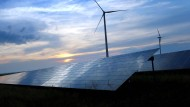 Solarkraftanlage und Windräder: Mit grünen Anleihen können Projekte im Bereich Erneuerbare Energien finanziert werden.