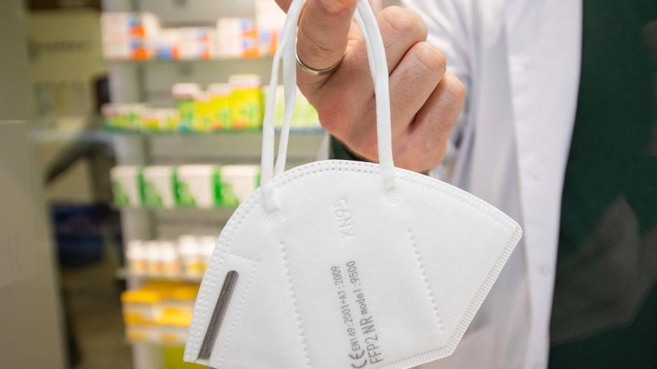 Ein Apotheker hält eine FFP2-Maske an einem Finger.