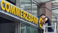 An den Börsen wird abgebaut: Ein Techniker arbeitet an einem Commerzbank-Schild an einer Filiale in Frankfurt.