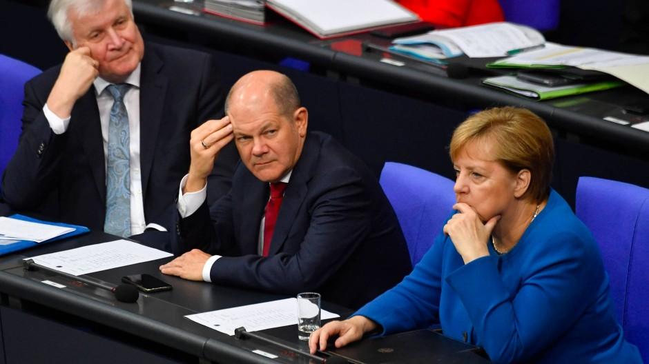 Die Reise nach Washington womöglich schon im Kopf, aber zumindest körperlich noch inmitten der Regierungsgeschäfte der GroKo: Finanzminister Olaf Scholz (Mitte).