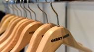 Leere Kleiderbügel mit dem Gerry-Weber-Logo hängen vor der Bilanzpressekonferenz in Halle an einer Garderobe.