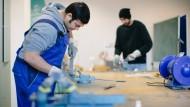 Probearbeiten in der Metallwerkstatt: Zwei Flüchtlinge in Dresden.
