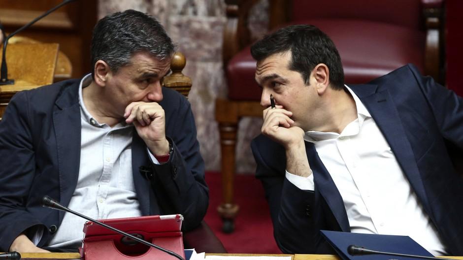Griechenlands Ministerpräsident Alexis Tsipras (r.) spricht während der Parlamentsdebatte mit seinem Finanzminister Euklid Tsakalotos.