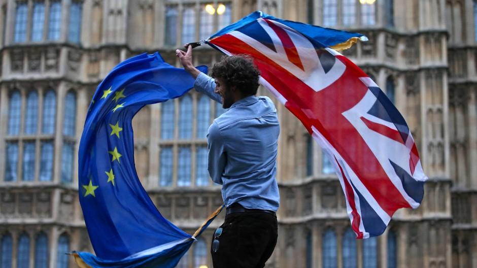 Grund zur Freude? Ein Mann mit einer britischen und einer europäischen Fahne