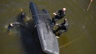 Polizisten, die an einer Vergleichsübung für Beweissicherungs- und Festnahmeeinheiten teilnehmen, versuchen, als Team ein Schlauchboot zu drehen.