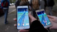 Pokémonspieler gehen in Berlin mit ihrem Handy durch die Straßen.