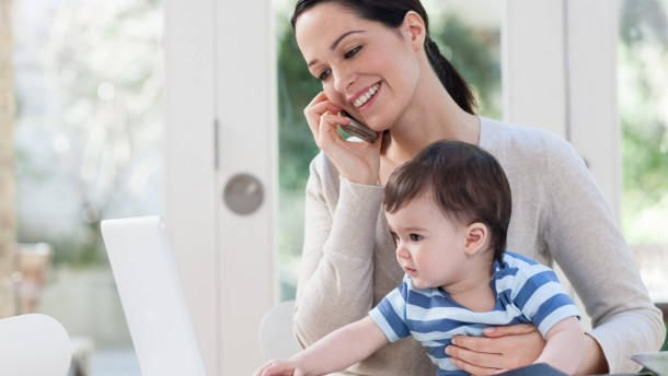 Mother on cellphone and baby looking at laptop