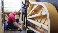"""Wunderwerk: Ein Tischler von Steinway & Sons arbeitet am selbstspielenden Konzertfügel """"Spirio""""."""