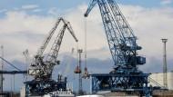 Wohin steuert der Handel? Im Rostocker Seehafen wird ein Schiff mit Kränen abgefertigt.