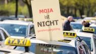 """Hamburg: Ein Schild mit der Aufschrift """"Moia ist nicht genehmigungsfähig"""" wird während eines Protests von Taxifahrern aus einem Taxi gehalten."""