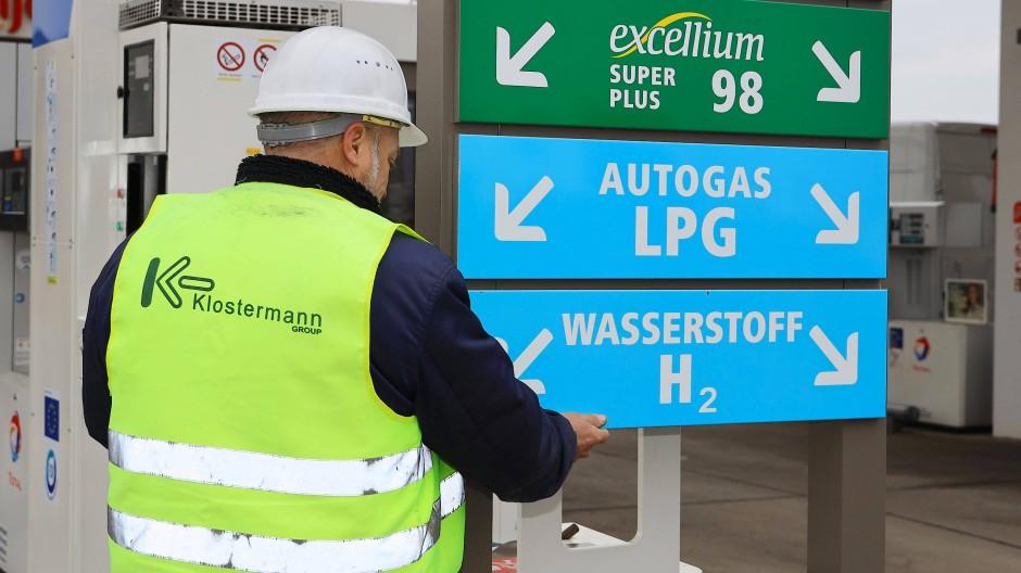 Ein Mitarbeiter bringt 2018 ein Hinweisschild an der ersten Wasserstofftankstelle in Sachsen-Anhalt an – die Nachfrage nach dem Energieträger steigt derweil in vielen Bereichen an.