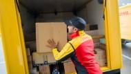 Ein Paketzusteller stellt ein Paket in ein Fahrzeug der Deutschen Post DHL.