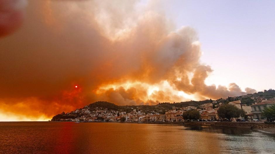 Griechenland erlebte dieses Jahr eine extreme Hitzewelle und verheerende Waldbrände. Rauch eines Waldbrandes steigt hinter einem Berghang in dem Ort Limni, auf der Halbinsel Euböa, etwa 160 Kilometer nördlich von Athen, auf.