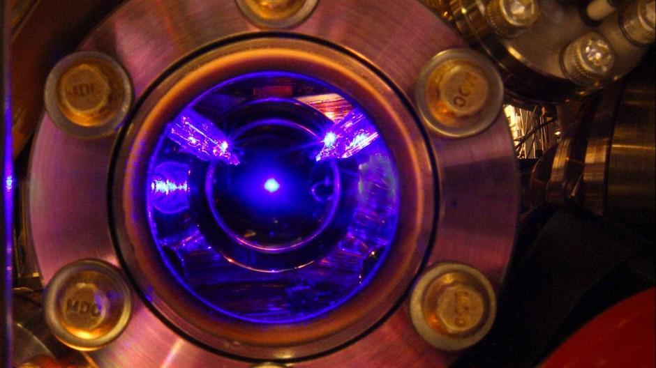 Blick in das Innere einer Strontium-Atomuhr: Strontium-Atome werden von Laserstrahlen in der Schwebe gehalten und erzeugen selbst ein blaues Leuchten.