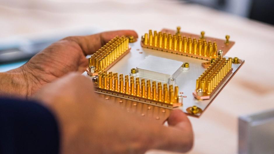 """In diesem silberglänzenden Kästchen verbirgt sich Googles  Quantenprozessor """"Sycamore"""". Über die vielen goldenen Kontakte wird er mit der Außenwelt verdrahtet und angesteuert."""