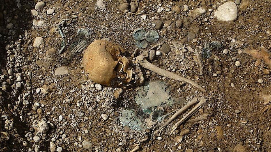 """Hochrangige Frauenbestattung aus Kleinaitingen, """"Gewerbegebiet Nord"""". Der Kopfschmuck und der Bestattungsritus spiegeln die lokalen Traditionen wider, aber Isotopenwerte zeigen die fremde Herkunft. Diese Bestattung einer Frau ist eine der reichsten bekannten Bestattungen Süddeutschlands."""