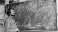 John Bell sinniert 1982 über sein Theorem. Ob Einstein oder die QM (für Quantenmechanik) recht hat, lässt sich damit überprüfen.