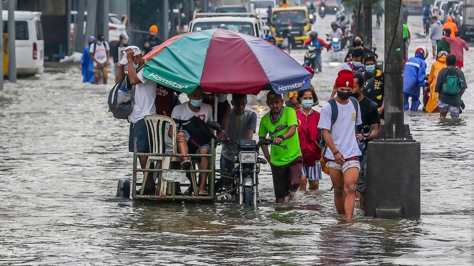 Menschen waten durch das Hochwasser, das im Juli durch starke Monsunregen in der philippinischen Provinz Rizal verursacht wurde.
