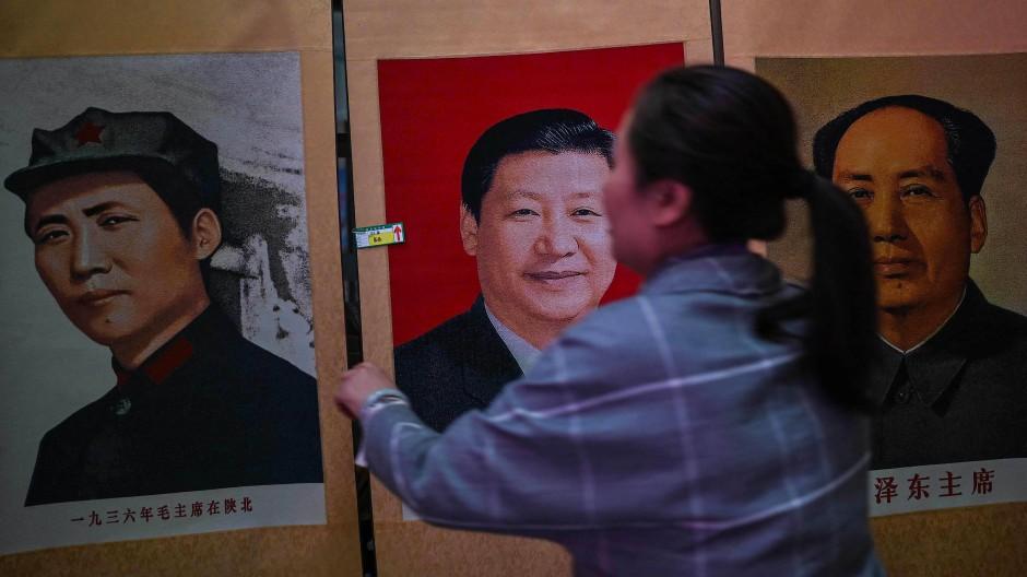 Chinas Präsident Xi Jinping (Porträt Mitte) sieht sich selbst in der Nachfolge Mao Tse-tungs und dessen Erbes verpflichtet.
