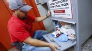 Ein Drogenermittler in Barberton öffnet eine Entsorgungsbox und findet tütenweise Opioid-Präparate.