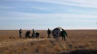 Rettungsmannschaften stehen neben der notgelandeten russischen Sojus-Kapsel in der Steppe von Kasachstan. Die beiden Astronauten sind wohlauf.