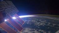 Das Nachthimmelsleuchten  der Mesopause sehen die Astronauten der Internationalen Raumstation als grünlich leuchtende Hülle, die die Erde umgibt.  Das Licht der untergehenden Sonne erscheint als heller Streifen.