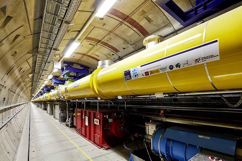 Blick in den 1,8  Kilometer langen Beschleunigertunnel des European XFEL mit den gelben supraleitenden Beschleunigermodulen.