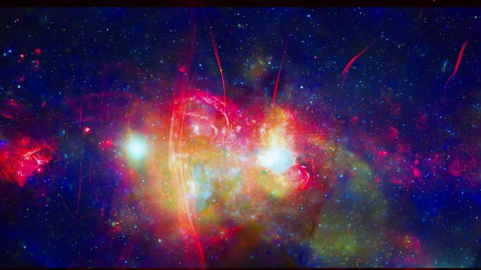 Die zentrale Region der Milchstraße, wo sich das Schwarze Loch Sagittarius A* befindet. Die Falschfarbenaufnahme ist eine Kombination von Beobachtungsdaten des Röntgensatelliten Chandra (grün und blau) und des Radioteleskops MeerKAT in Südafrika (rot).
