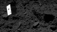 """Im freien Fall: Der kaum dreißig Zentimeter große Lander """"Mascot"""", aufgenommen von seiner Muttersonde vor dem Auftreffen auf Ryugu. Der Asteroid erhielt den Namen des Unterwasserpalastes eines mythischen Seedrachens."""