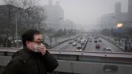 Ein Mann läuft mit Atemschutzmaske durch Peking
