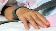 Eine mit einem Textilband festgebundene Hand eines fixierten Patienten.