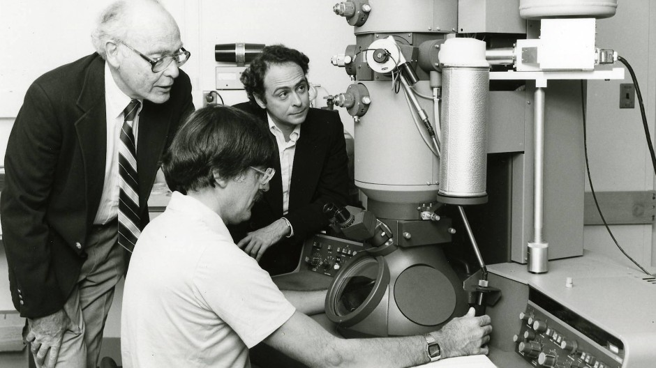 Daniel Shechtman 1985 vor seinem Elektronenmikroskop, mit dem er 1982 seine bahnbrechende Entdeckung machte. Im Hintergrund John Cahn und Denis Gratias (von links) vom National Institute of Standards and Technology (Nist).