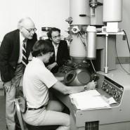 Daniel Shechtman 1985 vor seinem Elektronenmikroskop, mit dem er 1982 seine bahnbrechende Entdeckung machte. Im Hintergrund John Cahn und Denis Gratias (von links) vom National Institute of Standards and Technology (Nist).